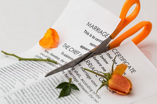 Marriage certificate being cut in half with scissors. at mediation.